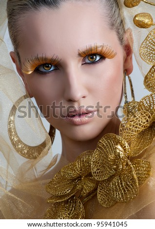 Vogue style portrait of a woman with gold makeup - stock photo