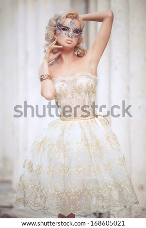 vogue style portrait of beautiful delicate woman in venetian mask and fashionable dress. Sexy woman in evening dress and carnival mask outdoors. soft focus. - stock photo