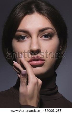 vogue style portrait of beautiful delicate woman with sensual lips on dark background