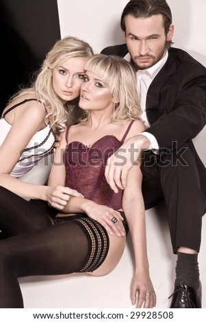 Vogue style studio shot of a man and 2 women - stock photo