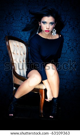 Vogue style vintage portrait of brunette model sitting on a chair