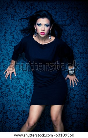 Vogue style vintage portrait of brunette model standing against the wall - stock photo