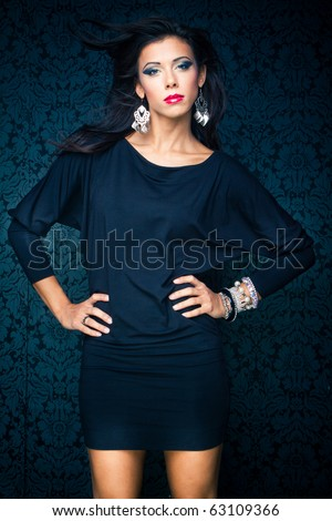 Vogue style vintage portrait of brunette model standing against the wall