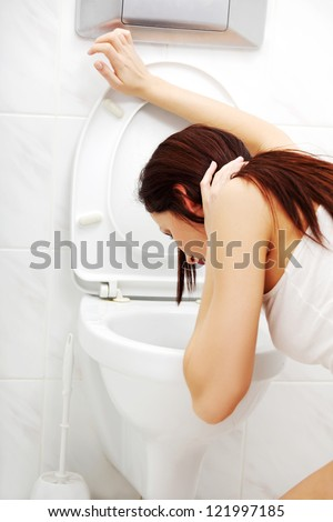 Voimiting woman in the bathroom in the morning.