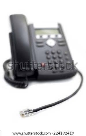 VOIP Phone I   Close up of a modern, digital VOIP (Voice Over IP) phone with selective focus on the network plug.