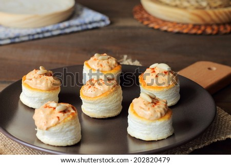 Vol-au-vents filled with seafood pate, paprika and pine nuts - stock photo
