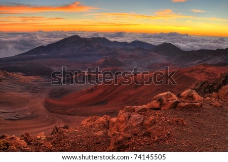 Volcanic crater landscape with beautiful orange clouds at sunrise taken at Haleakala National Park in Maui, Hawaii. - stock photo