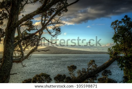 Volcanic island framed by a tree - stock photo
