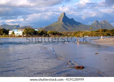 Volcanic mountain peaks at sunset on Tamarin beach Mauritius - stock photo