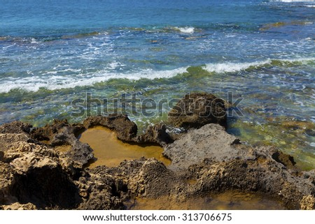 Volcanic rocks on the edge of clear sea water