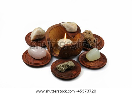 Volcanic stones on wooden plates and candle isolated on white