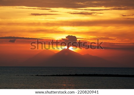 Volcano in Sumbawa erupting on sunset, view from Komodo national park