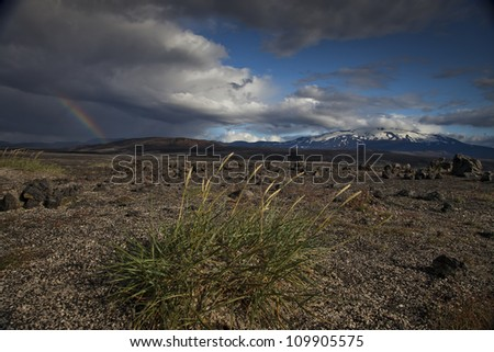 Volcano with rainbow and grass in the foreground - stock photo