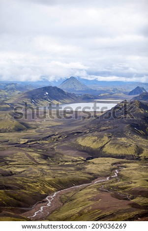 Volcanoes create a bizarre landscape of rhyolite rocks and green moss along the Landmannalaugar trek - stock photo