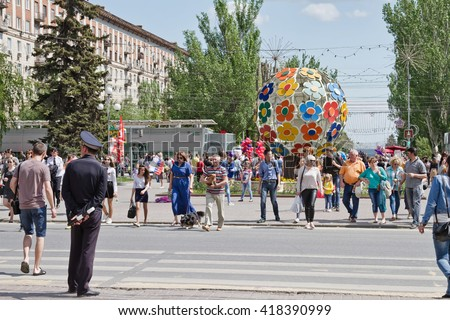 "VOLGOGRAD - MAY 9: A large number of tourists on may 9, people cross the road at the alley of heroes, near the sculpture ""Tree of peace"". May 9, 2016 in Volgograd, Russia."
