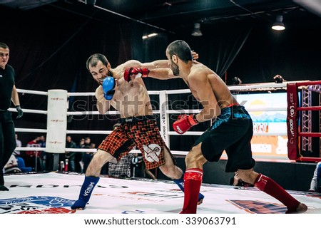 Volgograd, Russia - October 24, 2015: mixed martial arts fighter deals a direct blow to hand on head of opponent during Championship of Russia on mixed martial arts - stock photo