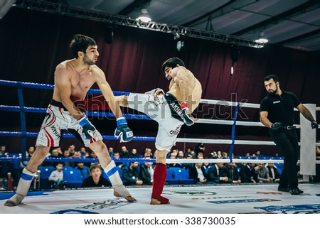 Volgograd, Russia - October 24, 2015: MMA fighter direct kick in belly of an opponent during Championship of Russia on mixed martial arts - stock photo