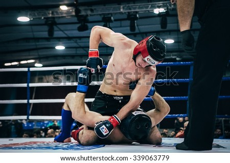 Volgograd, Russia - October 24, 2015: MMA fighter gets a direct hit a hand on head of an opponent lying on floor ring during Championship of Russia on mixed martial arts - stock photo