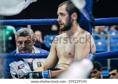 Volgograd, Russia - October 24, 2015: MMA fighter sit in corner of ring during break between rounds during Championship of Russia on mixed martial arts - stock photo