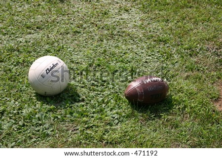 Volleyball and football in the grass. - stock photo