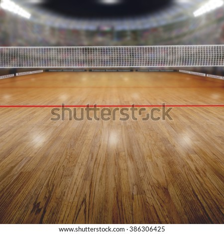 Volleyball arena full of fans in the stands with deliberate focus on foreground and shallow depth of field on background net and court. Floodlights flare for effect and copy space. - stock photo