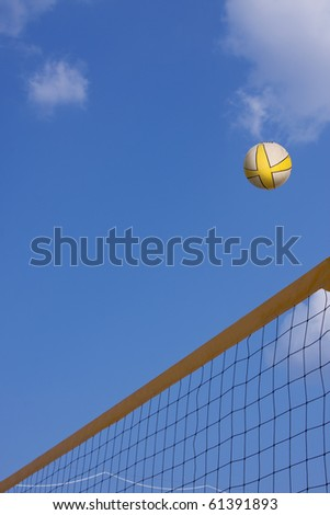 volleyball in the air over the net with copy space - stock photo