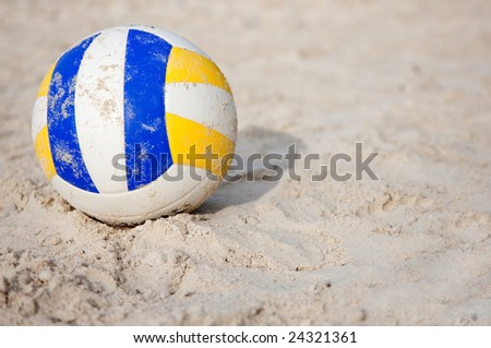 Volleyball lying still on the sand at a beach