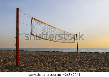 volleyball net against the beach on sunrise - stock photo