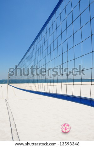 Volleyball net and ball on pretty white beach by ocean - stock photo