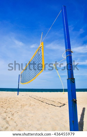 Volleyball net on beach with blue sky and sea, vertical - stock photo