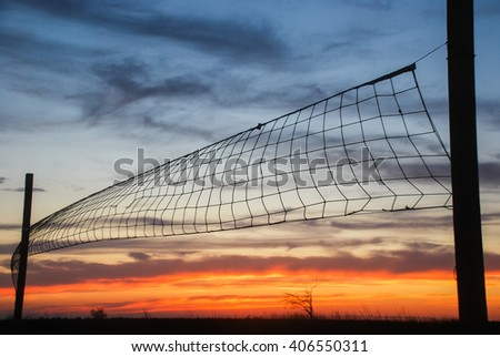 Volleyball net on sunset sky background in the desert - stock photo