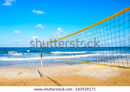 volleyball net on the beach close-up. blue cloudy sky and yellow sand on the beach - stock photo