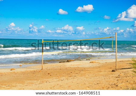 volleyball net on the beach. cloudy blue sky and turquoise sea - stock photo