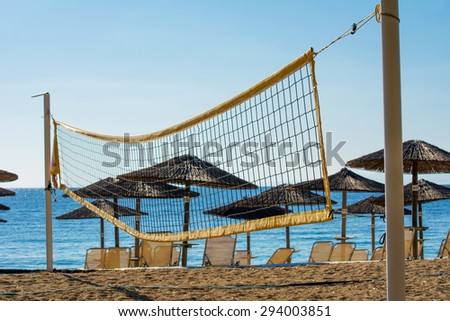 Volleyball net on the beach with umbrellas and chairs in the background - stock photo