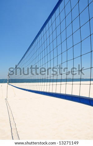 Volleyball net set up on beautiful white beach under blue sky - stock photo