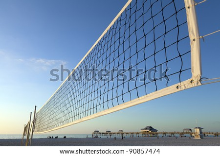 Volleyball net stretched on the beach ready for a game in the afternoon. - stock photo