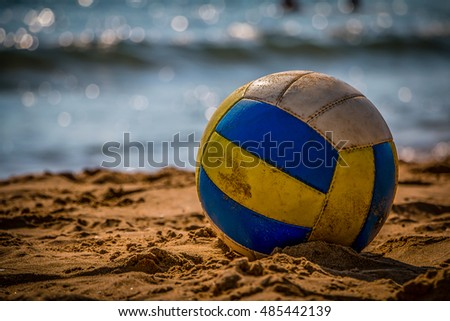 Volleyball on yellow sand on empty beach in twilight