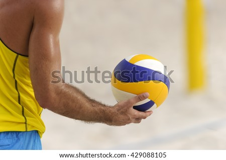 Volleyball player is a male athlete getting ready to serve the ball.