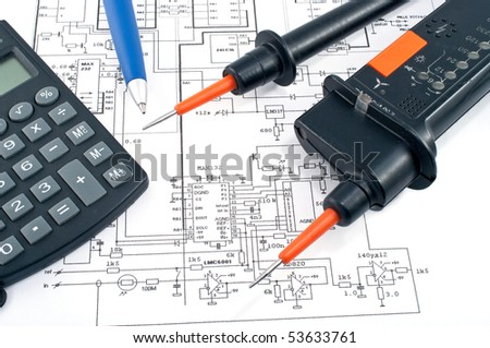 Voltage tester,calculator  and pen on electrical diagram - stock photo