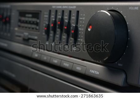 Volume and graphic equalizer controls on an audio system shot with low key light and selective focus - stock photo