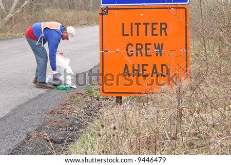 Volunteer collecting litter along country road - stock photo