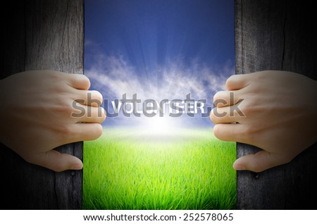 Volunteer concept. Hand opening an old wooden door and found a texts floating over green field and bright blue Sky Sunrise. - stock photo