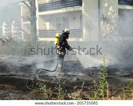 Volunteer Firefighter fighting for a fire attack above a house - stock photo
