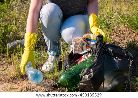 Volunteer girl in yellow gloves collects garbage selective focus - stock photo