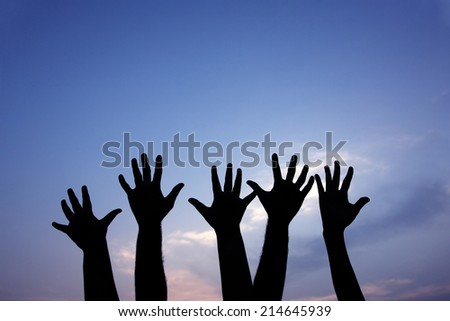 volunteer group raising hands against blue sky background  - stock photo