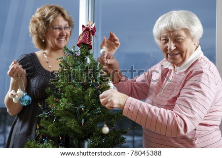 Volunteer helping senior decorate her Christmas Tree - stock photo