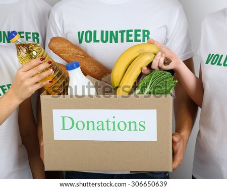Volunteer holding donation box with food, closeup - stock photo