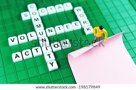Volunteer key words on game boards and miniature people holding blank post-it - stock photo