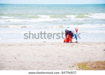 volunteer man cleaning on beach - stock photo