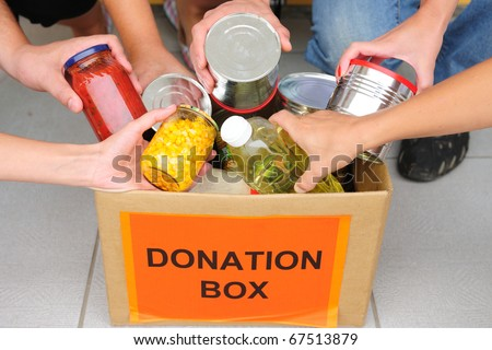 volunteer putting food in a donation box - stock photo